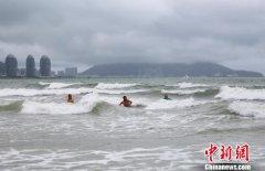"""台风""""山神""""横穿海南 游客不惧风雨三亚海边嬉水"""